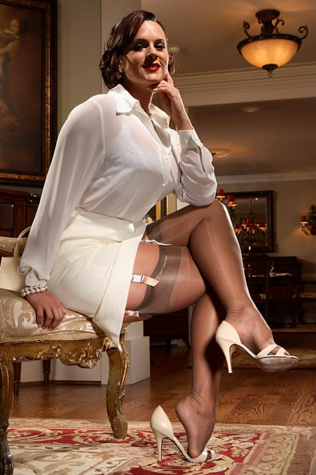 Зрелая дама сексуально сидит в кресле показывая свои ноги в нейлоновых чулках на поясе