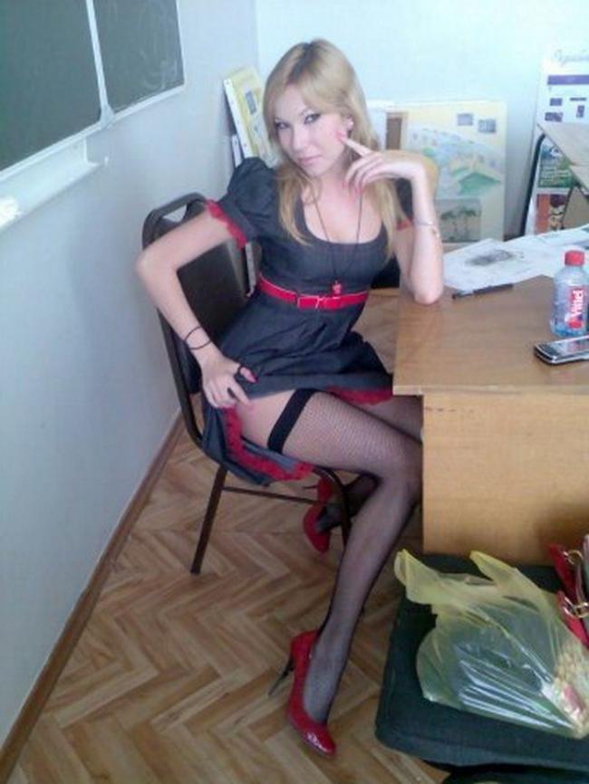 Блондинка училка в коротком платье кокетливо приподнимает юбку показывая ножки в чулках