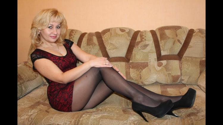 Зрелая блондинка сидеть на диване вполоборота в колготках туфли на высоком каблуке