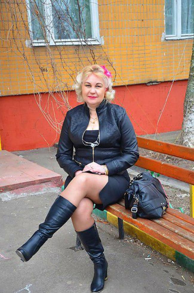 Зрелая блондинка в кожаной короткой юбке, высоких сапожках сидит на лавочке