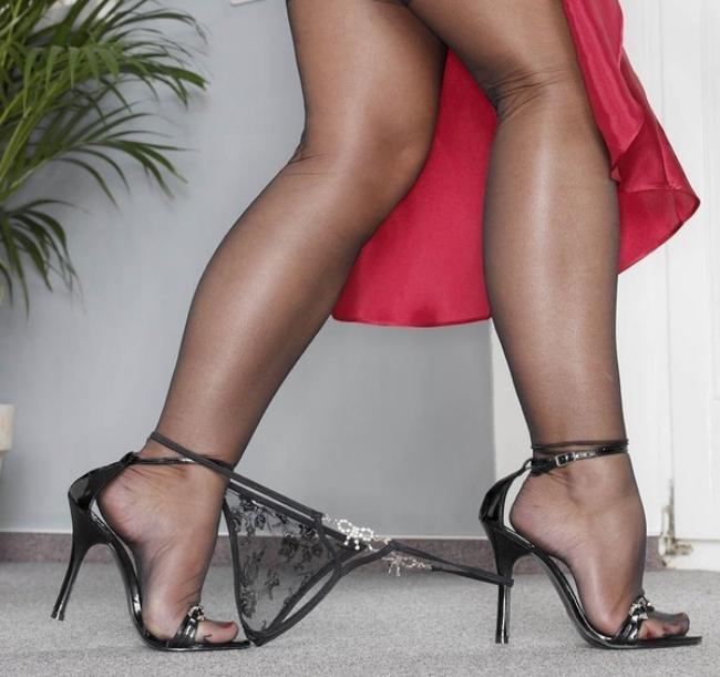 Ножки полные в чулочках в босоножках на каблуках с опущенными стрингами