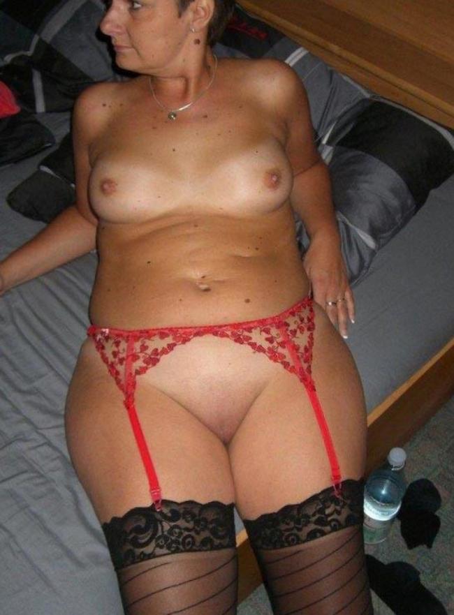 Мадам голая в пизда бритая лежит в кровати черные чулки