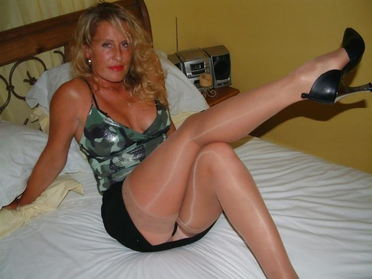 В короткой юбке и топике лежит на кровати в чулках телесного цвета подняв ногу