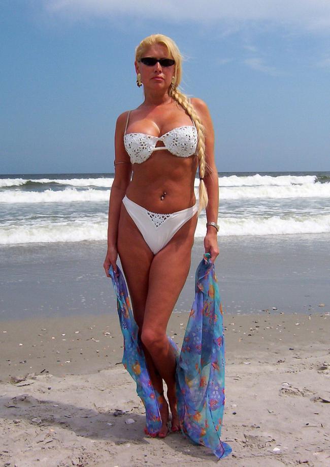 Шикарная загорелая блондинка с косой в белом купальнике на берегу моря