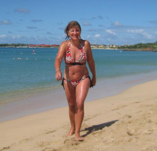 Зрелая в цветном купальнике идет по пляжу улыбается