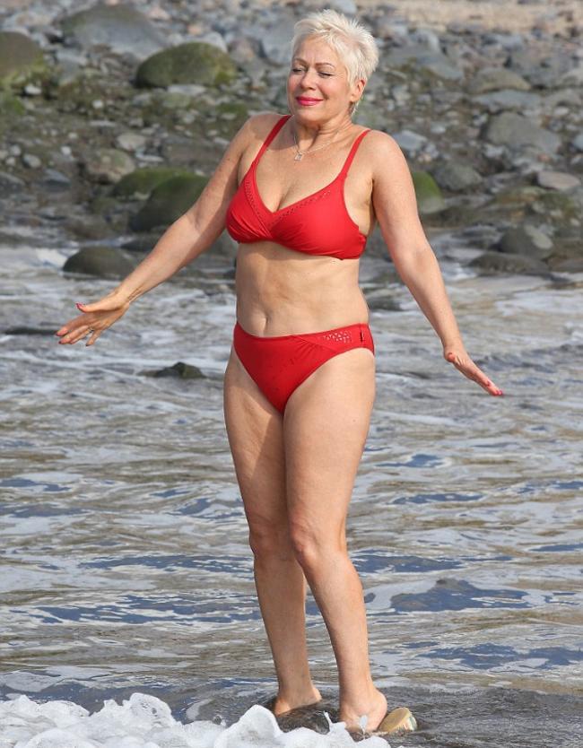 Зрелая красотка в красном купальнике заходит в море эмоционально
