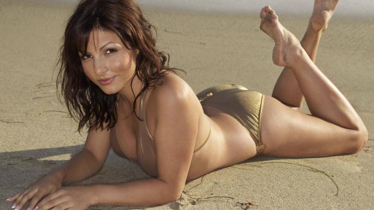 Красивая женщина лежит ена песке на животе подняв эротично ножки