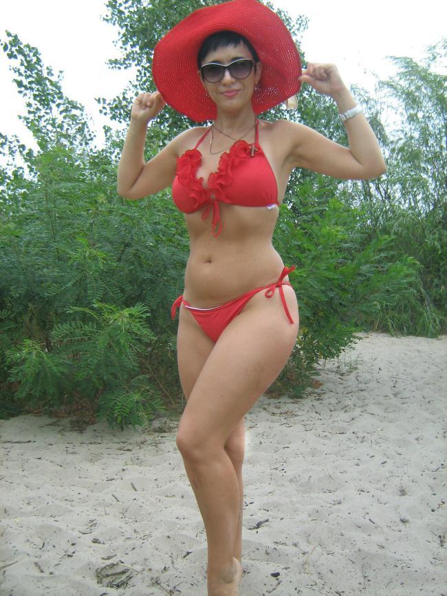 Красотка в шикарном красном купальнике красной шляпе с обалденной фигурой