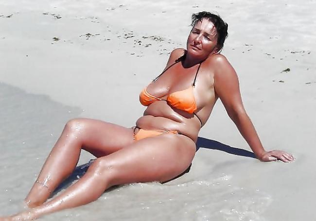 Зрелая женщина у кромки воды сидит в купальнике