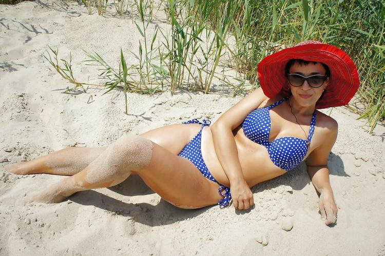 Купальник в горошек песок красная шляпка на красивой зрелой женщине
