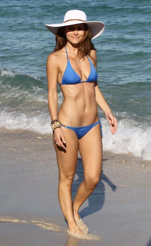 Красивая зрелая стоит в голубом бикини на берегу, в шляпе