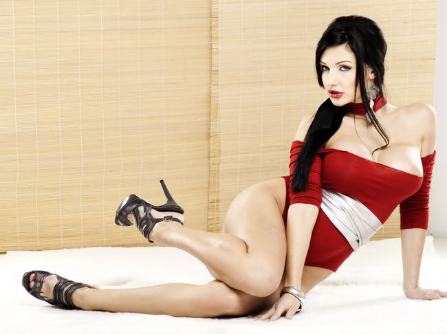 Алетта Оушен фото на белой кровати в красном боди на ногах туфли на высоком каблуке, губы накрашены яркой помадой, рот приоткрыт