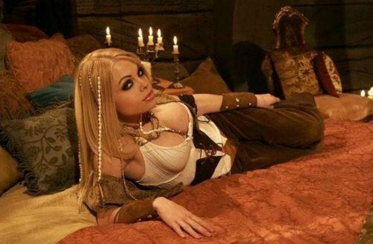 Джесси Джейн по пояс в белых шортахлежит на кровати в костюме пиратки