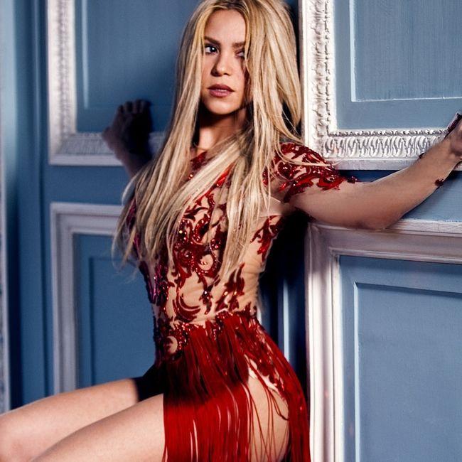 Шакира фото в ярком концертном костюме, сидя на коленях прижалась к стене