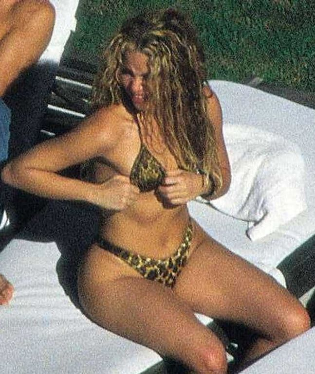 Шакира поправляет свой лифчик.