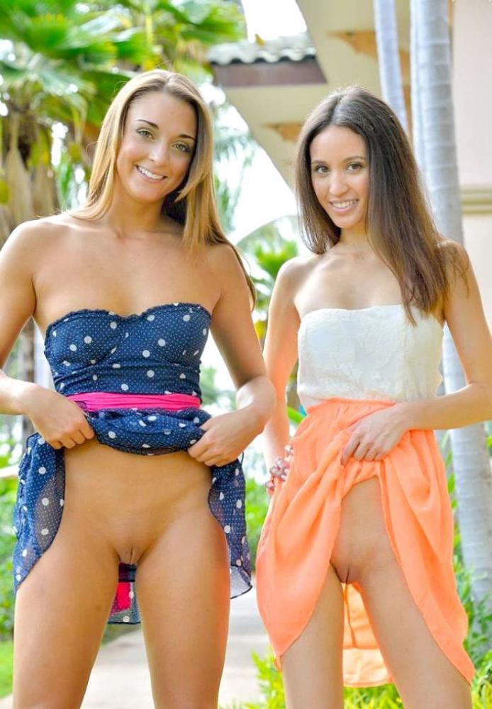 Две девушки в коротких юбках подняли подол и показывают бритую пизду и мило улыбаются.