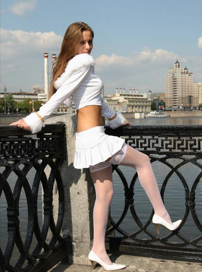 молодая девушка в белой короткой юбке белых чулках, белая кофточка, белые туфли.