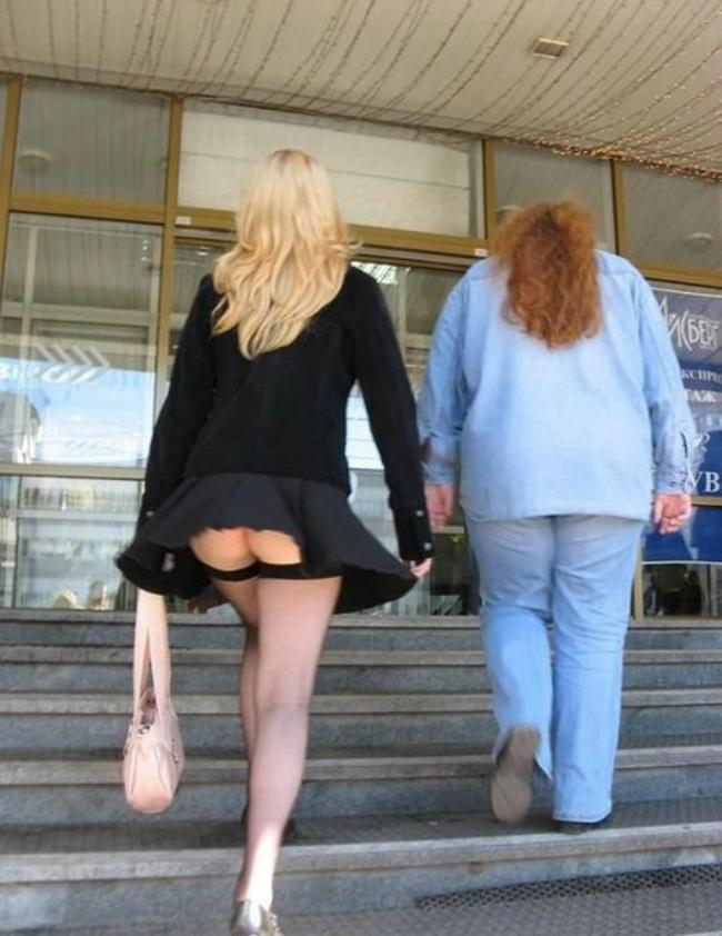 Блондинка поднимается по лестнице вид сзади, ветер поднял короткую юбку обнажив задницу, ножки в чулках.