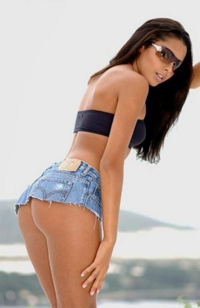 Красивая юрюнетка в очень короткой джинсовой юбке.