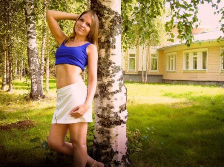 Девушка в короткой юбке белой и синем топике обножив живот стоит у березы подняв правую руку держит голову, мило улыбается