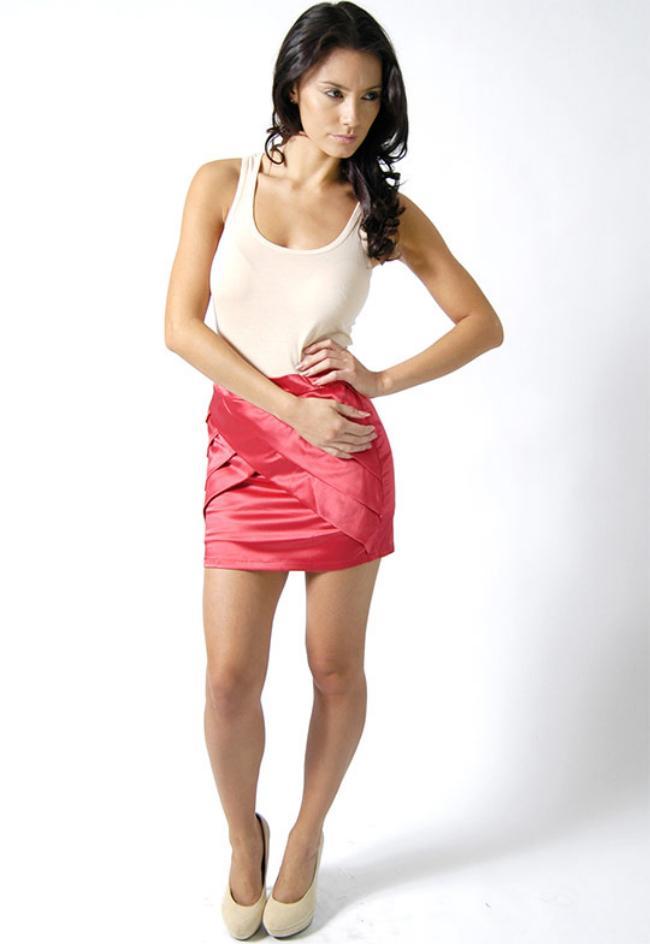 Красивая девушка в короткой юбке красной и белой маечке позирует