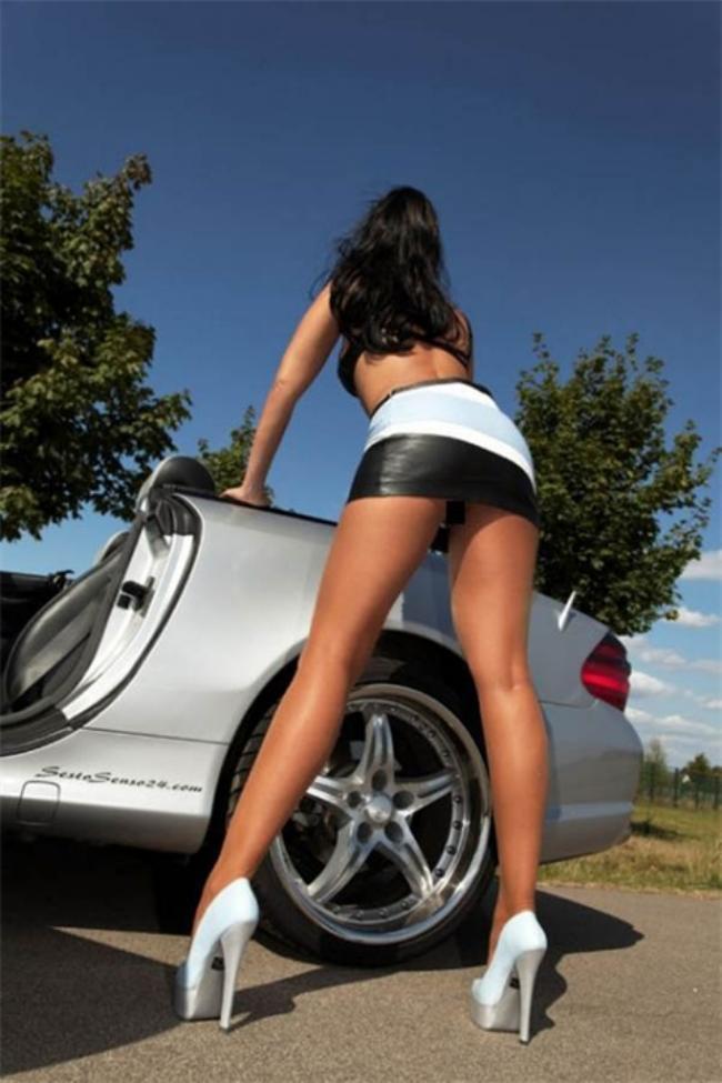 Стоит возле автомобиля вид сзади шикарные ноги, туфли на высоком каблуке, короткая юбка.