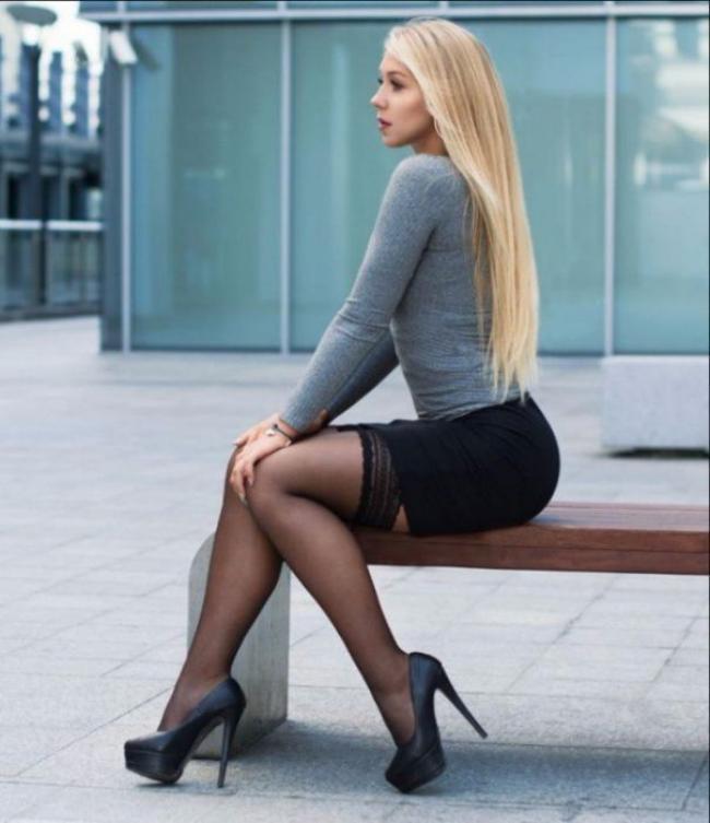 Сидит на скамейке в короткой юбке, ноги в чулках, туфли на высоком каблуке, длинные волосы.