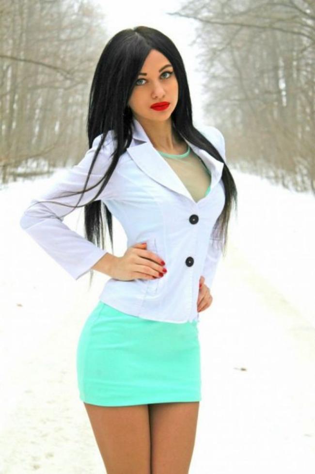 Девушка в короткой обтягивающей юбке ярко-зеленого цвета и белой блузке стоит на зимней дороге, красивые черные волосы и призывный взгляд