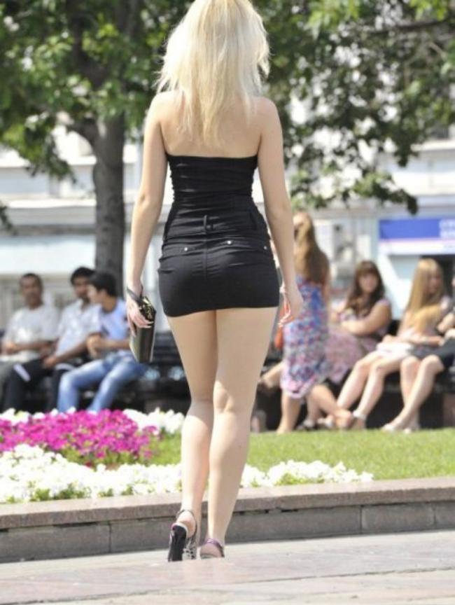 Блондинка со спины в короткой черной юбке.