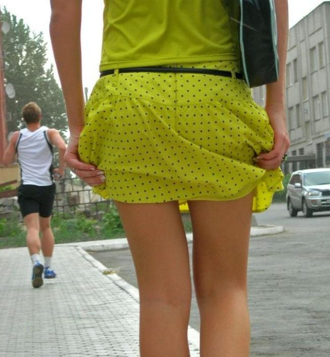 Девушки в короткой юбке вид сзади короткая желтая юбка в черный горошек идет придерживает руками идя по мощеному плиткой тротуару