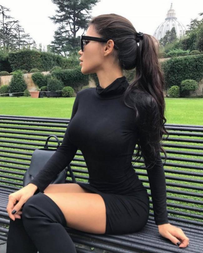 Шикарная брюнетка в красивом черном коротком платье сидит на лавочке.