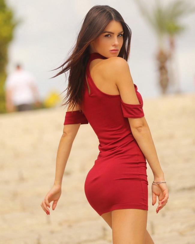 Красивая в красном коротком платье со спины.