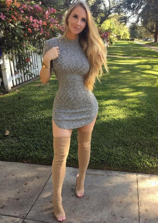девушка с большой грудью в обтягивающем сером платье выше колена стоит на фоне лужайки