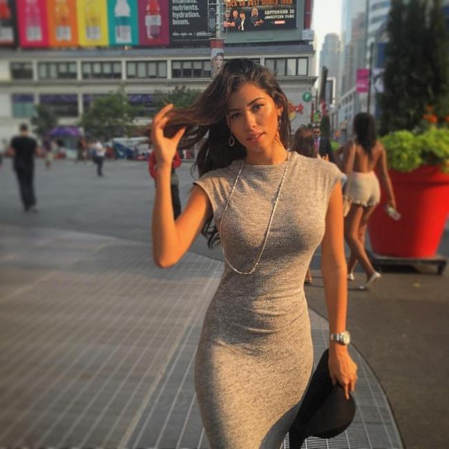 девушка в обтягивающем платье идет по площади и машет рукой