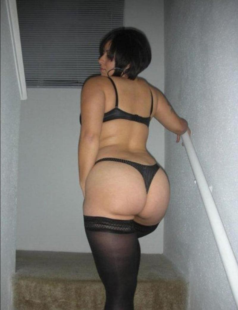 попа зрелой женщины брюнетка с короткой стрижкой стоит на лестнице в черных чулках с хорошей фигурой