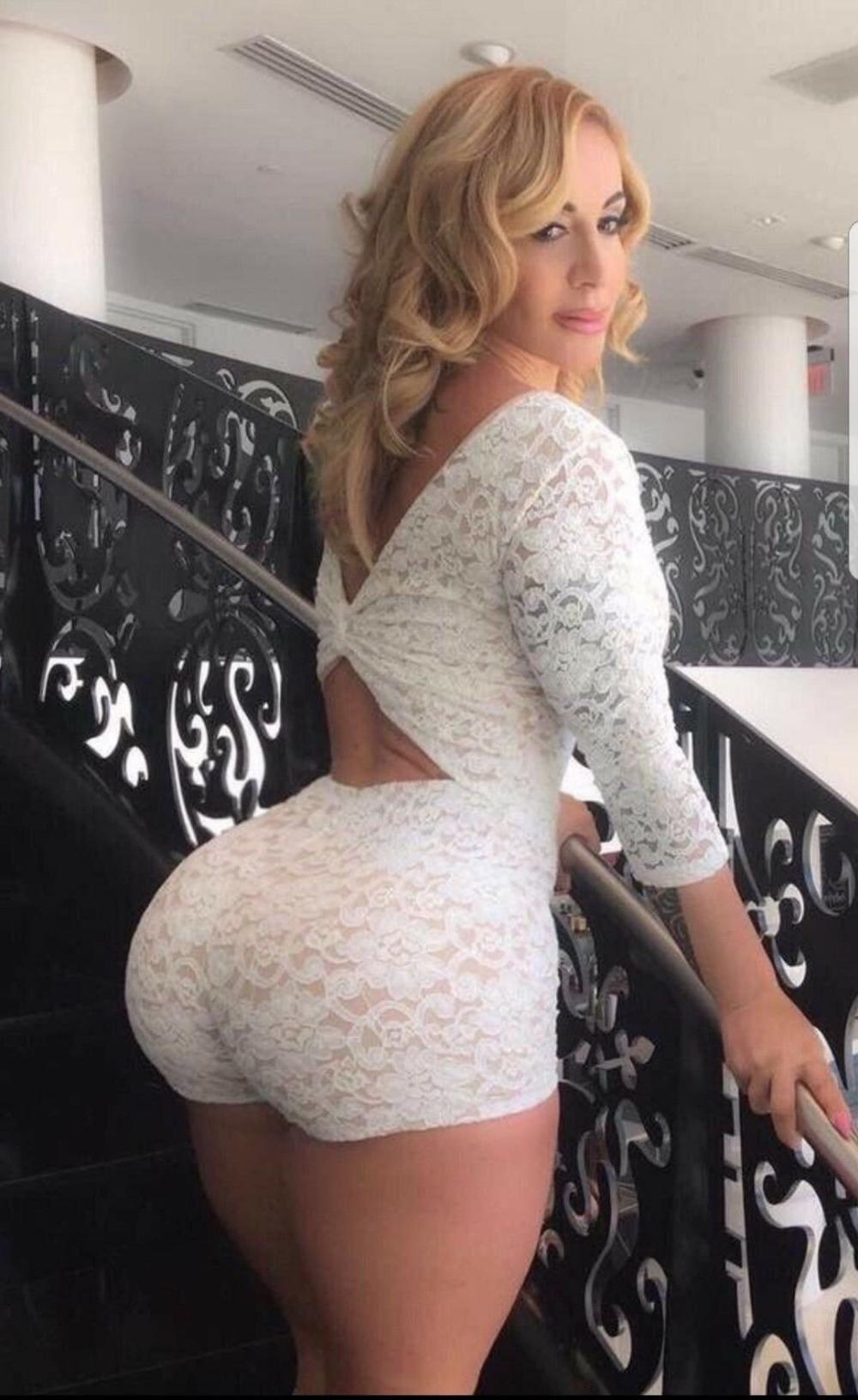 красивая зрелая попа шикарной блондинки стоит на лестнице в белом гипюровом костюме шорты обтянули зад и кофточка