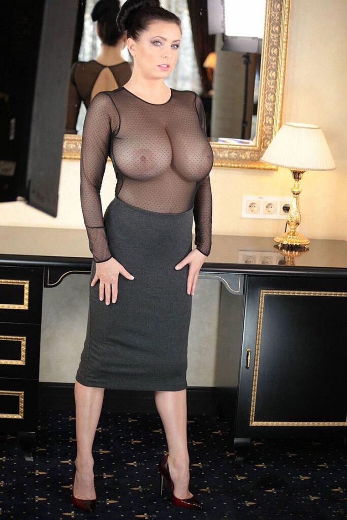 Зрелые тетки, шикарная женщина лет 45 стоит в полупрозрачном топе черного цвета, видны соски на большой груди, волосы собраны в пучок, ноги на ширине плеч, руки положила вдоль бедер, на ногах туфли на высоком каблуке