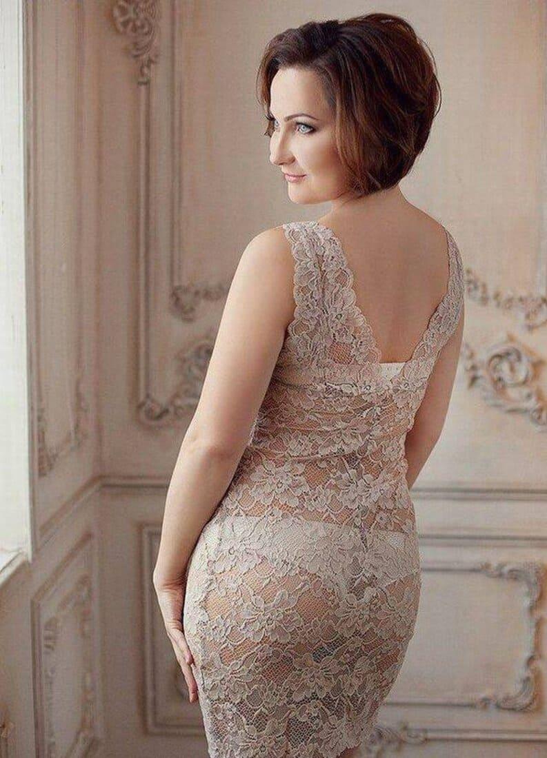 зрелая женщина в светлом обтягивающем гипюровом платье, через которое просвещается нижнее белье стоит повернувшись спиной фото