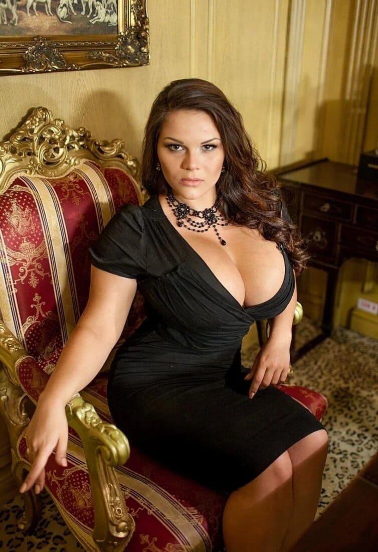 Красивая зрелая женщина с темным длинным волосом в черном обтягивающем платье с большим декольте и сиськами сидит в кресле приоткрыв немного колени фото