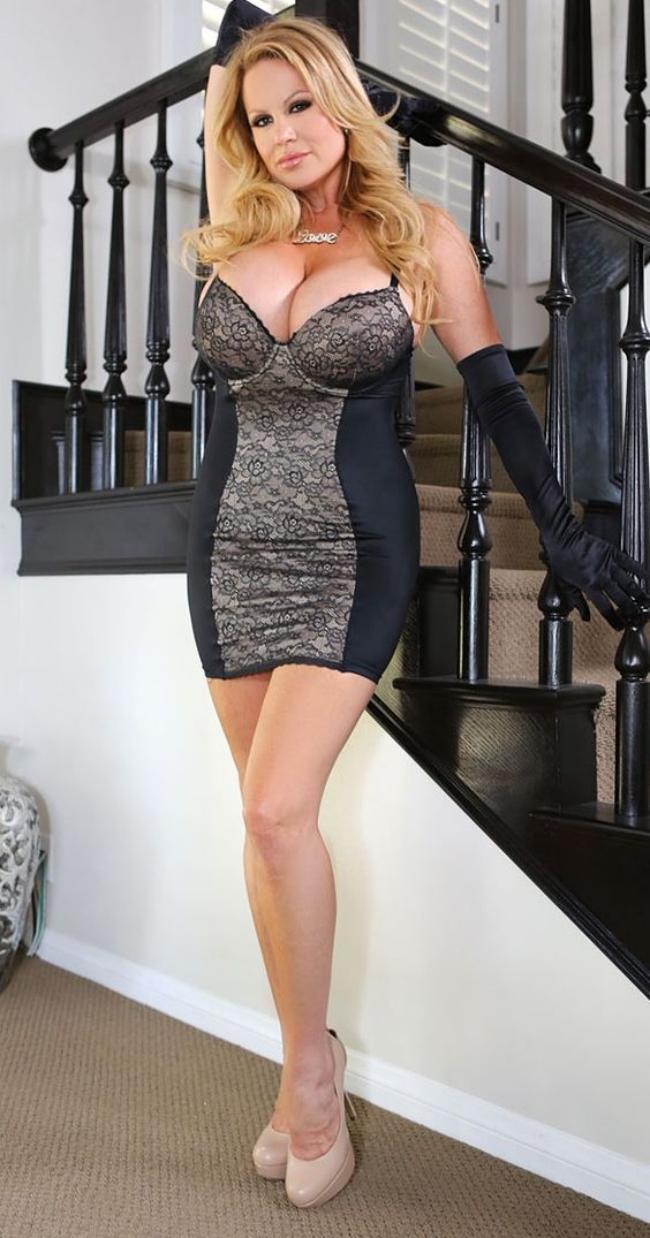 Красивая зрелая женщина в обтягивающем мини платье блондинка, туфли на каблуке, шикарный бюст