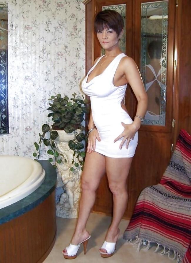 шикарная зрелая женщина в обтягивающем платье мини белого цвета, короткая стрижка, сиськи выпирают, туфли на высоком каблуке