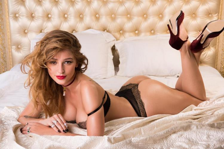 фото Анастасия Ивлеева лежит в черном белье и туфлях на кровати в бордовых туфлях на высоком каблуке волосы распущены губы накрашены ярко-красной помадой