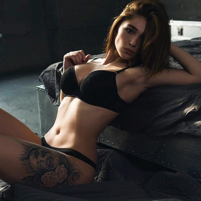Анастасия Ивлеева сидит в черном сексуальном белье опираясь спиной на кровать