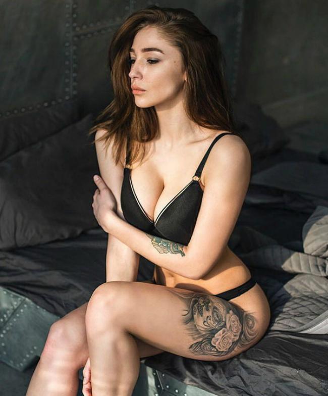 Анастасия Ивлеева фото в сексуальном белье черного цвета сидит на кровати смотрит прямо перед собой на левой ноге и на руке видны татуировки