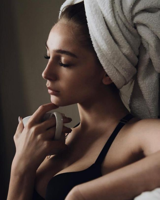 Анастасия Ивлеева фото с закрученным на голове полотенцем с кружкой в руке и лифчике задумчиво смотрит перед собой