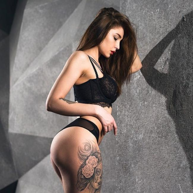 Анастасия Ивлеева фото позирует у стены в сексуальном белье черного цвета на ноге видна татуировка волосы распущены