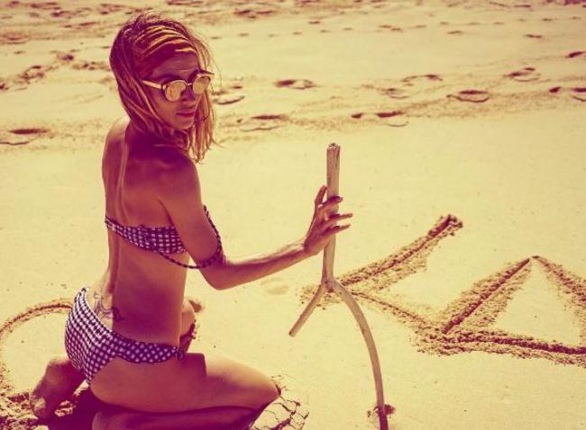 Светлана Лобода фото в купальнике на пляже сидит на коленях, вид сбоку рисует палкой на песке