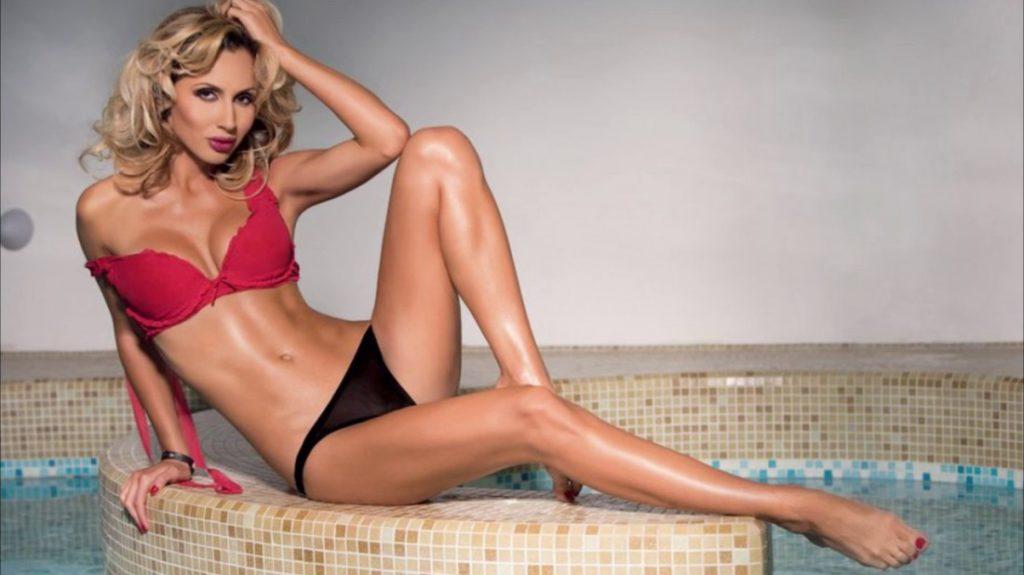 Светлана Лобода фото в бассейне сидит на краю в красном бюстике и черных плавках, левая нога согнута в колене