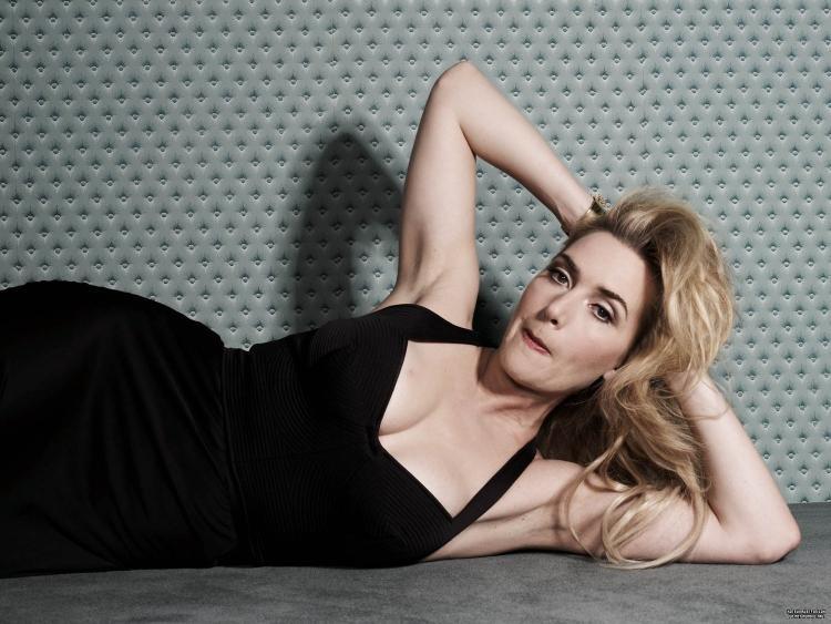 Кейт уинслет фото лежит на боку в черном платье с открытыми плечами и глубоким декольте, руки подняты на голову, подмышки открыты