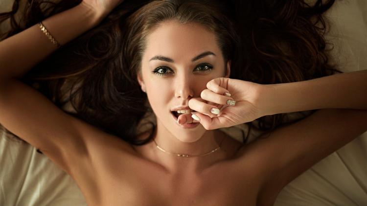 Девушка прикусила зубами палец палец